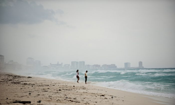 A couple walks in Playa del Carmen beach, Quintana Roo State, mexico on October 25, 2011.  (Schemidt/AFP/Getty Images)