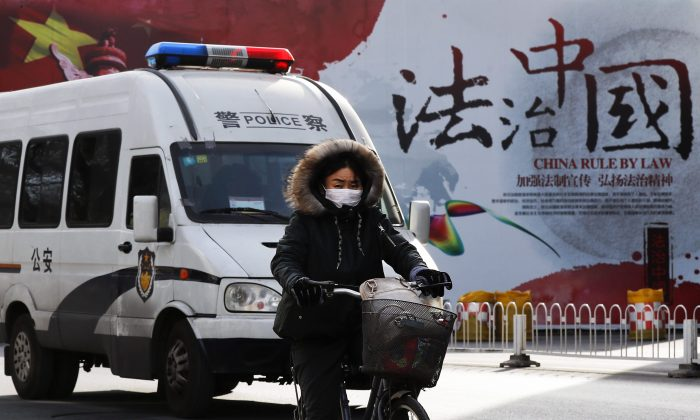 A police van and a cyclist pass a government propaganda billboard on a street in Beijing on Dec. 28, 2016. (AP Photo/Andy Wong)
