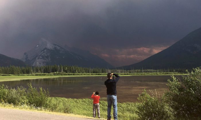 Tourists at Banff National park take photos of Mt.Rundle and the Vermillion Lakes as smoke from a forest fire in Kootenay National park blankets the area, July 15, 2017. (The Canadian Press/Adrian Wyld)