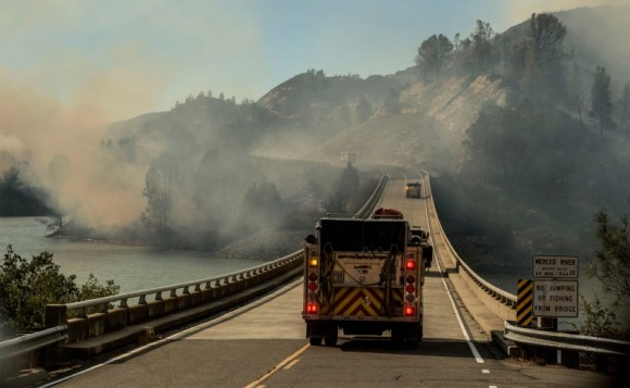 A firetruck drives across the Merced River at the Bagby bridge after authorities ordered evacuations due to the Detwiler fire in Mariposa, California, U.S. July 18, 2017. (Reuters/Al Golub)