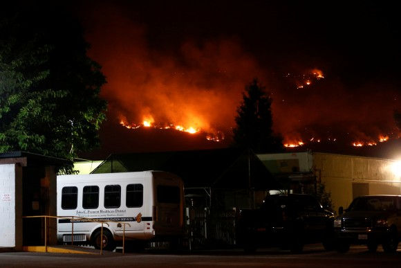 Flames from the Detwiler fire burn on a hill near the John C. Fremont Hospital in Mariposa, California, U.S., July 18, 2017. (Reuters/Stephen Lam)