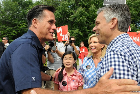 Republican presidential candidates Former Ambassador to China Jon Huntsman (R) and former Massachusetts governor Mitt Romney (L) greet to each other prior to marching in a Fourth of July parade as Huntsman's wife Mary Kaye (2nd R) and daughter Gracie Mei look on July 4, 2011 in Amherst, New Hampshire. (Photo by Darren McCollester/Getty Images)
