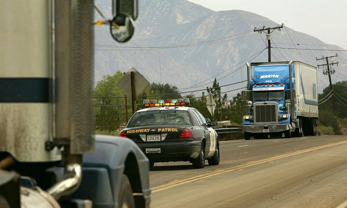 A wayward trucker approaches a highway patrolman at a roadblock. (Photo by David McNew/Getty Images)