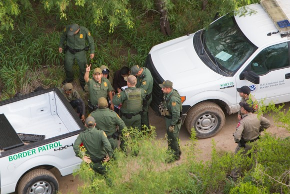 A Border Patrol agent signals to the Customs and Border Protection helicopter crew that two aliens from a group of seven they tried to capture have escaped, near Salineno, Texas, on May 30. (Benjamin Chasteen/The Epoch Times)