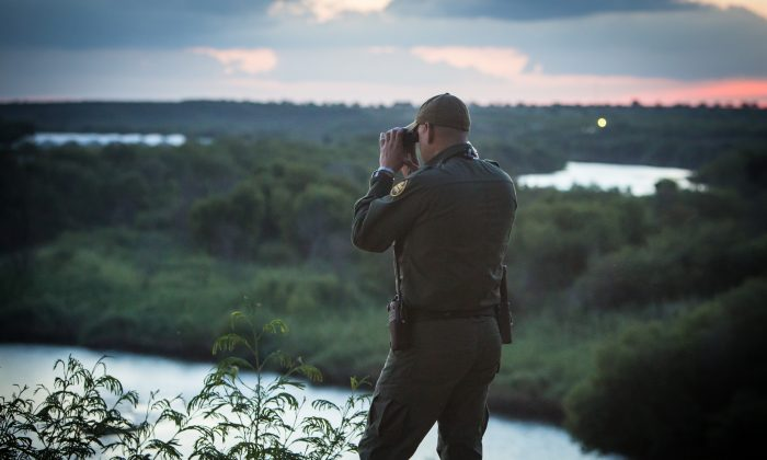 A Border Patrol agent on the lookout for illegal aliens crossing the Rio Grande from Mexico into Texas as the sun sets in the city of Roma on May 31. (Benjamin Chasteen/The Epoch Times)