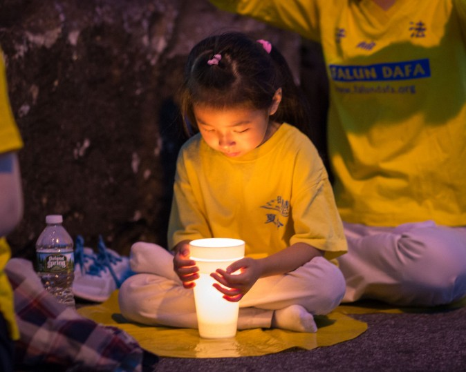 A little girl attends a candlelight vigil in front of the Chinese Consulate in New York on July 16, 2017. (Benjamin Chasteen/The Epoch Times)