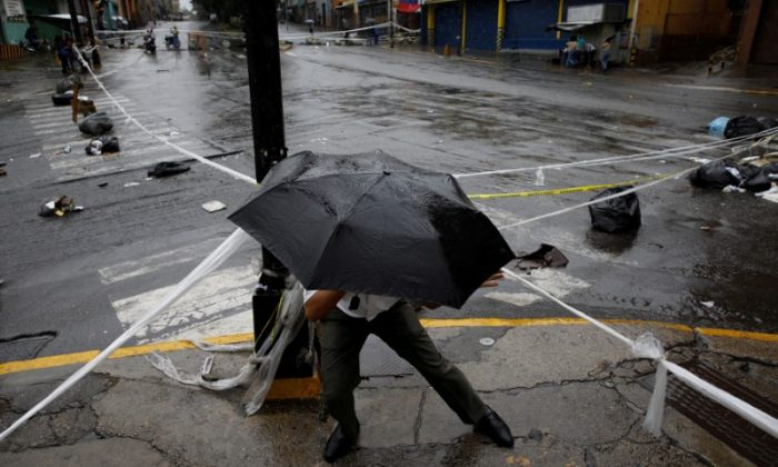 A pedestrian walks through a barricade during a rally against Venezuelan President Nicolas Maduro's government in Caracas, Venezuela, July 19, 2017.  (Reuters/Carlos Garcia Rawlins)