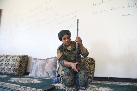 Heza, a Yazidi fighter from the Shengal Women's Units (YPS), a group of women fighters from Iraq's northeastern Sinjar region supporting the Women's Protection Units (YPG), prepares her rifle in an abandoned home used by the YPS as their base in Al-Meshleb, on the eastern outskirts of Raqa on July 18, 2017.  (BULENT KILIC/AFP/Getty Images)