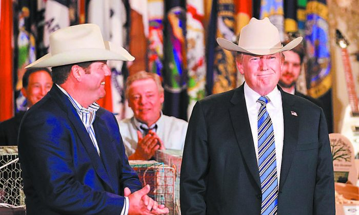 President Donald Trump wears a Stetson cowboy hat given to him by Dustin Noblitt, CEO of RHE Hatco (L), while touring a Made in America product showcase in the White House on July 17. (CHIP SOMODEVILLA/GETTY IMAGES)