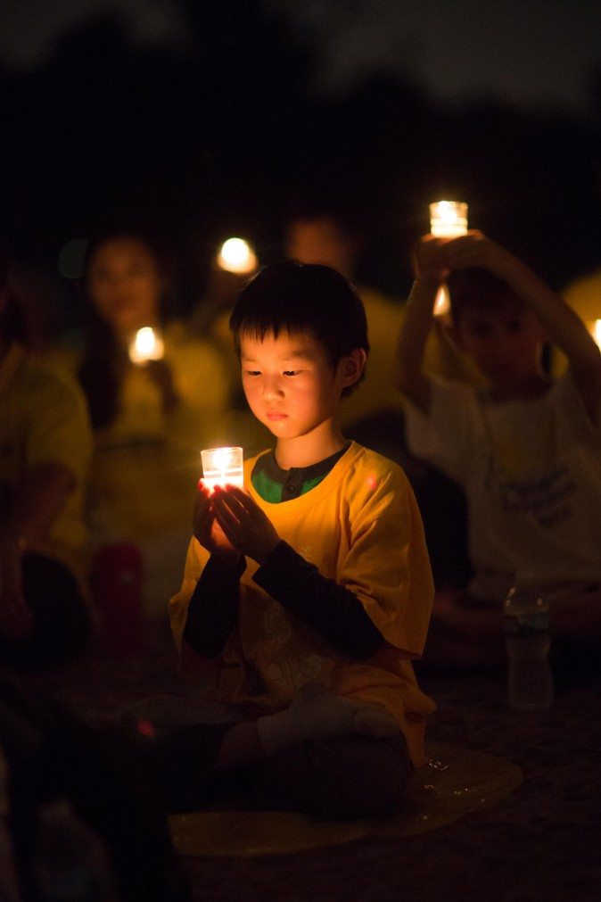 A little boy joins Falun Gong practitioners hold a candlelight vigil at the Lincoln Memorial in Washington on July 20, 2017, to honor those who have died during the persecution in China that the Chinese regime started on July 20, 1999. (Benjamin Chasteen/The Epoch Times)