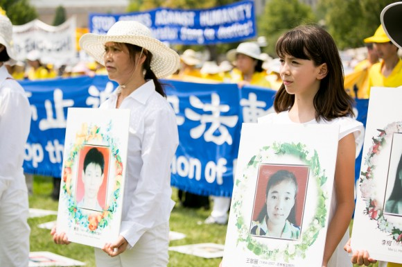 Two Falun Gong practitioners protest the brutal persecution and deaths of Falun Gong practitioners in China at a rally in Washington, D.C. on July 20. They are holding the photos of two victims of the persecution. (Lisa Fan/ Epoch Times)
