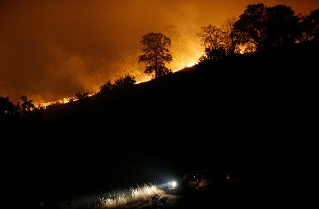 A firefighting truck is seen parked along a firebreak beneath a burning ridge during the Detwiler fire in Mariposa, California. (Reuters/Stephen Lam)