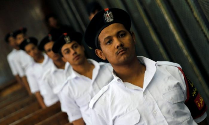 Police officers stand guard as defendants accused of involvement in the 2015 assassination of Egypt's top prosecutor attend a hearing in a cage in a courtroom, on the outskirts of Cairo, Egypt, June 17, 2017. (Reuters/Amr Abdallah Dalsh)