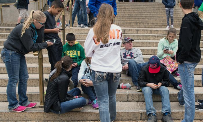 A group of teens check their smartphones outside the Natural History Museum in Washington on April 8, 2015. A Pew Research Center survey released found that 92 percent of US teens go online daily.  (NICHOLAS KAMM/AFP/Getty Images)