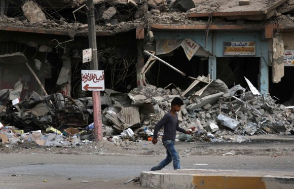 """A boy walks along a damaged street in west Mosul on July 13, 2017, a few days after the government's announcement of the """"liberation"""" of the embattled city from Islamic State (IS) group fighters. / AFP PHOTO / SAFIN HAMED        (Photo credit should read SAFIN HAMED/AFP/Getty Images)"""
