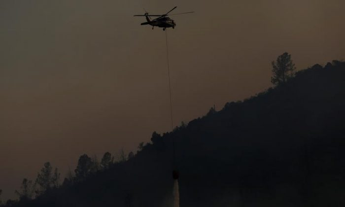 A helicopter makes a water drop on a hot spot during the Detwiler fire in Mariposa, California U.S. July 19, 2017. (Reuters/Stephen Lam)