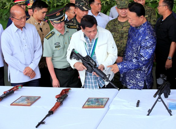 """File photo: Philippine President Rodrigo Duterte inspects an automatic rifle while Defense Secretary Delfin Lorenzana (L), Wang Xianyun (2-L) military and defence attache of the People's Republic of China and H.E. Zhao Jianhua (R), ambassador of China to the Philippines look on, during the turnover ceremony of China's urgent military assistance, given """"gratis"""" to the Philippines at Clark Air Base, Philippines June 28, 2017. (Reuters/Romeo Ranoco)"""