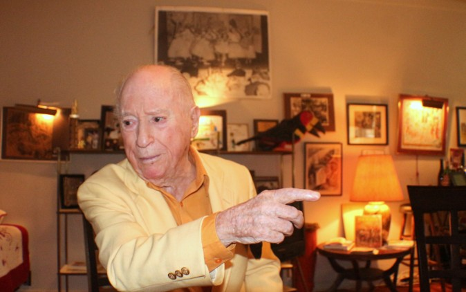 At home in his Brownstone apartment in New York City Irwin Hasen points to some of the many comic book covers and cartoon art that decorate the walls. (Myriam Moran copyright 2014)