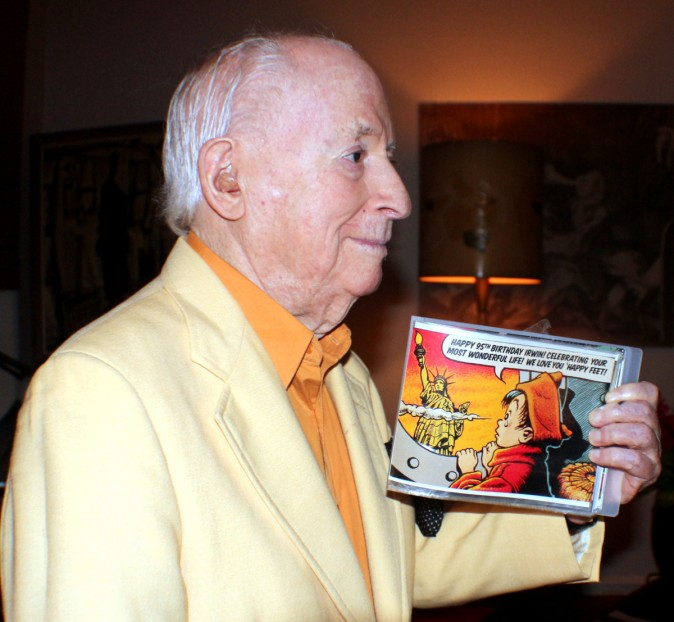 Irwin Hasen with a memento book of pictures and his cartoon art made for his 95th birthday. (Myriam Moran copyright 2014)