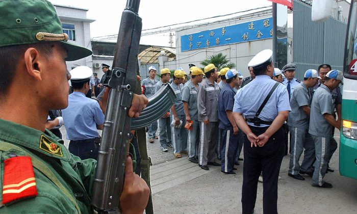 Prisoners wait in line to board a bus under police and armed military escort, 16 August 2004 in Zhengzhou, in central China's Henan Province. (STR/AFP/Getty Images)