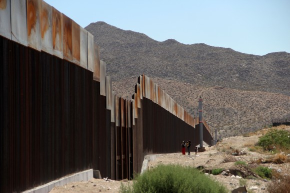A Mexican family stands next to the border wall between Mexico and the United States, in Ciudad Juarez, Mexico on May 23, 2017.  (HERIKA MARTINEZ/AFP/Getty Images)