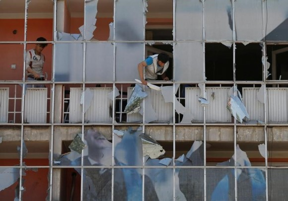 An Afghan man removes fragments of glass from a building after a suicide attack in Kabul, Afghanistan July 24, 2017. (Reuters/Mohammad Ismail)