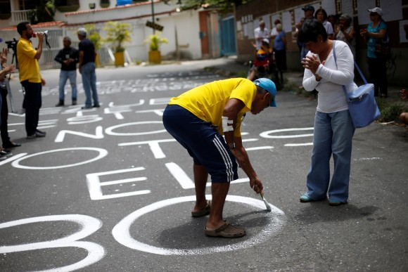 An opposition supporter paints on the road outside a school during a rally against the National Constituent Assembly, outside a school where a polling center will be established for a Constitutional Assembly election next Sunday, in Caracas, Venezuela, July 24, 2017. (Reuters/Andres Martinez Casares)