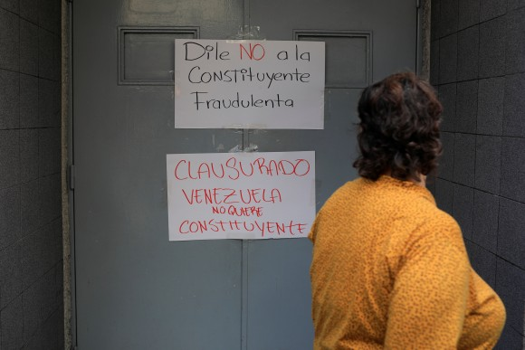 "A woman walks past placards that read ""Say no to the fraudulent constituent"" (top) and ""Closed. Venezuela does not want constituent"" at the door of a school where the polling center will be established for a Constitutional Assembly election next Sunday, in Caracas, Venezuela July 24, 2017. (Reuters/Marco Bello)"