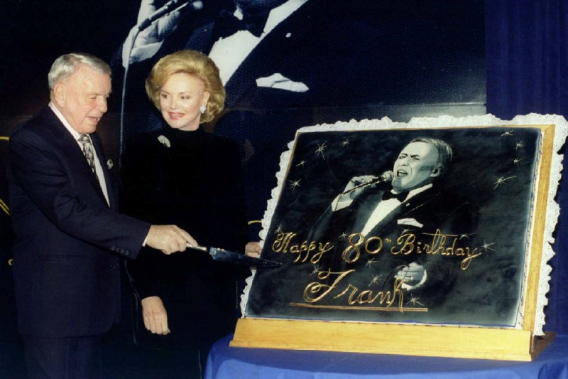 FILE PHOTO - Music legend Frank Sinatra, joined by his wife Barbara, cuts an oversize 80th birthday cake during a ceremony in his honor, at a New York hotel in New York City, U.S. on November 30, 1995.   REUTERS/Mark Cardwell/File Photo