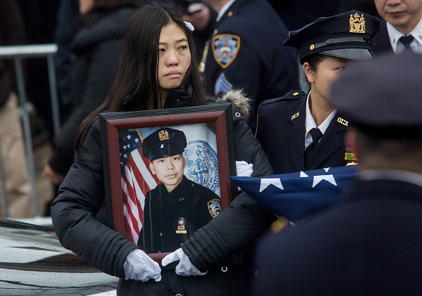 Pei Xia Chen, the widow of New York City Police Officer Wenjian Liu, holds his picture following his funeral service at Aievoli Funeral Home in the Dyker Heights neighborhood on Jan. 4, 2015 in the Brooklyn borough of New York City. Liu was killed with his partner Rafael Ramos on December 20, 2014 when the two were shot by Ismaaiyl Brinsley while sitting in their patrol car. (Eric Thayer/Getty Images)