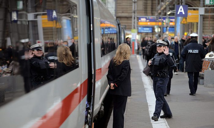A Train conductor speaks with a policewoman next to the latest generation of the ICE 3 Deutsche Bahn high-speed train during a media presentation on February 18, 2014 at Frankfurt, Germany. The train, built by Siemens, has a top speed of 320km per hour for the admission in France. In Germany the top speed is around 300km per hour.  (Photo by Thomas Lohnes/Getty Images)