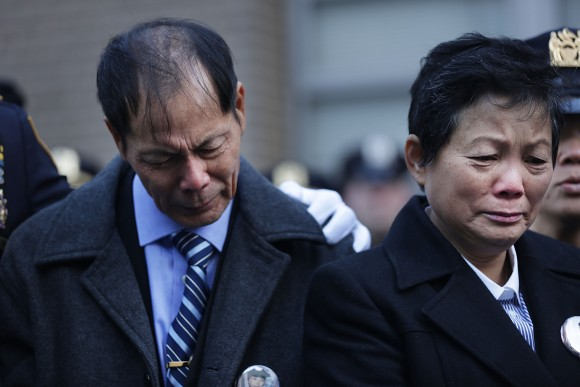 Wei Tang Liu (L), the father of Detective Wenjian Liu, grieves during a plaque dedication ceremony for two fallen New York Police Department  officers, Detective Rafael Ramos and his partner Detective Wenjian Liu at the 84th Precinct in Brooklyn on Dec. 20, 2015 in New York City. Detectives Ramos and Liu were fatally shot while sitting in their patrol car in Bedford-Stuyvesant one-year prior. The gunman, Ismaaiyl Brinsley, then killed himself.  (Spencer Platt/Getty Images)