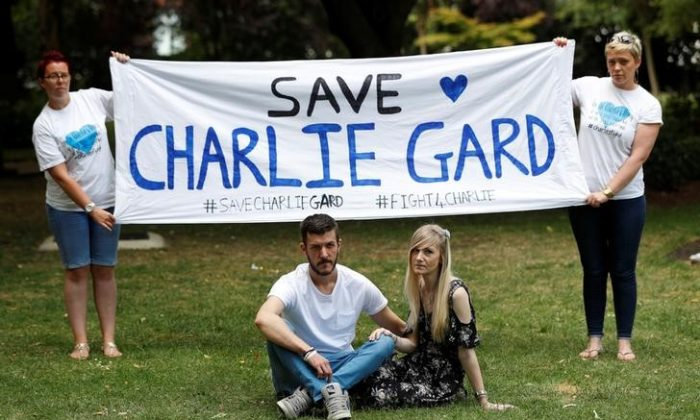 The parents of critically ill baby Charlie Gard, Connie Yates and Chris Gard, pose for photographers  as supporters hold a banner, before delivering a petition to Great Ormond Street Hospital, in central London, Britain July 9, 2017. (Reuters/Peter Nicholls/Files)