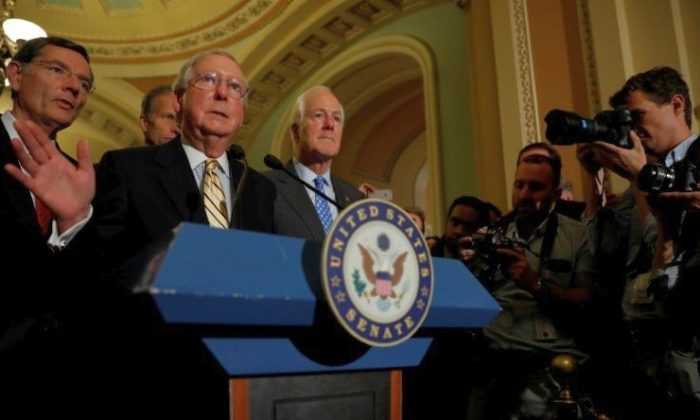 Senate Majority Leader Mitch McConnell, accompanied by Senator John Cornyn (R-TX) and Senator John Barrasso (R-WY), speaks with reporters following the successful vote to open debate on a health care bill on Capitol Hill in Washington on July 25, 2017. (REUTERS/Aaron P. Bernstein)