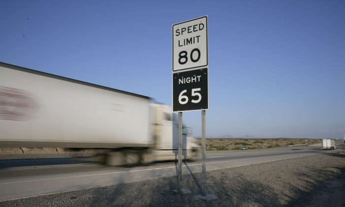 Trucks pass by a sign indicating the highest speed limit in the country as they travel down Interstate 10 outside of the West Texas town of El Paso on  July 21, 2006.  (Rick Scibelli/Getty Images)