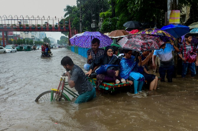 Commuters use a rickshaw to cross a flooded street amid heavy rainfall in Dhaka, Bangladesh, on July 26, 2017. Bangladesh is experiencing downpours following a depression forming in the Bay of Bengal. (MUNIR UZ ZAMAN/AFP/Getty Images)