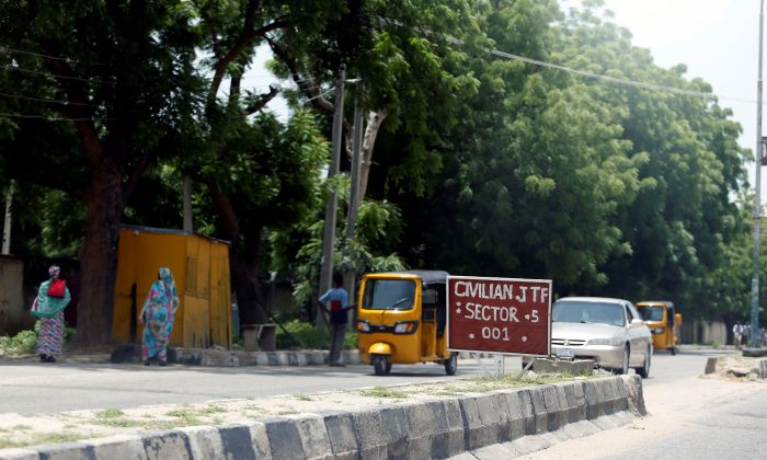 A car drives towards a Civilian Joint Task Force (CJTF) sector 5 sign in Maiduguri, Nigeria August 30, 2016. (Reuters/Afolabi Sotunde)