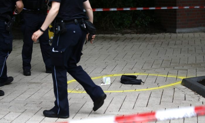 A police officer walks past crime scene after a knife attack in a supermarket in Hamburg, Germany. One person was killed and several were injured in an attack by a lone knifeman in a supermarket in the northern German city on Friday, police said.  (Reuters/Morris Mac Matzen)