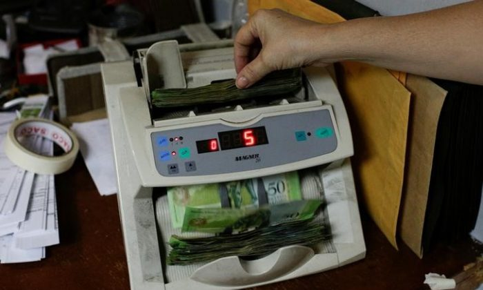 A woman uses a machine to count Venezuelan bolivar notes at an office in Caracas, Venezuela March 21, 2017. (Reuters/Marco Bello)