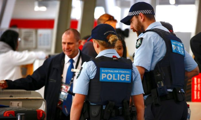 Australian Federal Police officers talk with passengers near the check-in counters at the Sydney Airport Domestic terminal in Australia, July 30, 2017. (Reuters/David Gray)