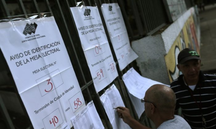 People check electoral lists before voting during the Constituent Assembly election in Caracas, Venezuela, July 30, 2017. (Reuters/Marco Bello)