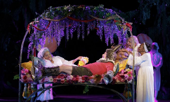 """Queen Titania (Phylicia Rashad) dotes on the weaver Nick Bottom who's been transformed into an ass (Danny Burstein), while her fairy servants (L–R, Warren Wyss, Vinie Burrows, and Keith Hart) attend to all of his needs, in perhaps the most famous scene in """"A Midsummer Night's Dream."""" (Joan Marcus)"""