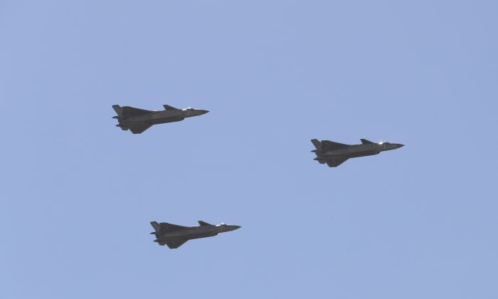 Chinese J-20 stealth fighter jets fly past during a military parade at the Zhurihe training base in China's northern Inner Mongolia region on July 30, 2017. China held a parade of its armed forces on July 30 to mark the 90th anniversary of the People's Liberation Army (PLA) in a display of military might. / AFP PHOTO / STR / China OUT        (Photo credit should read STR/AFP/Getty Images)