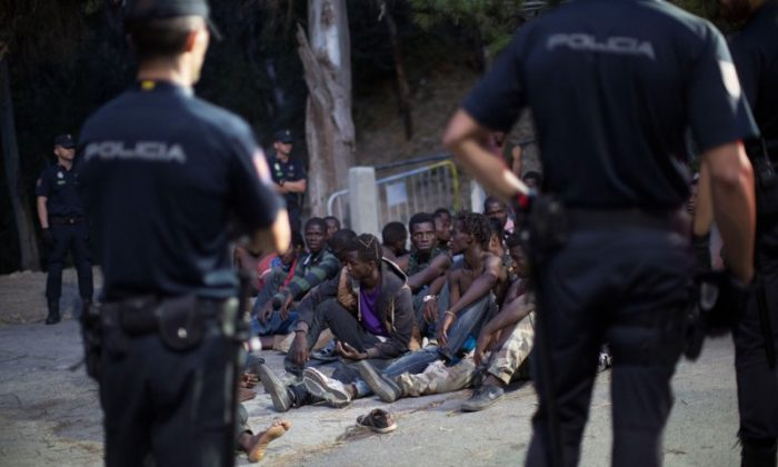Police stand around a group of African migrants after they crossed the border fence from Morocco to Spain's North African enclave of Ceuta, Spain Aug. 1, 2017.  (Reuters/Jesus Moron)