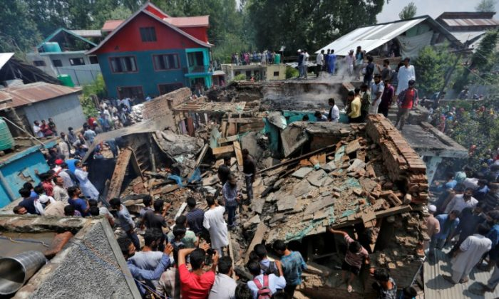 People stand on the rubble of a house after it was damaged during a gunbattle between militants and Indian security forces in Hakripora in south Kashmir's Pulwama district August 1, 2017. (Reuters/Danish Ismail)