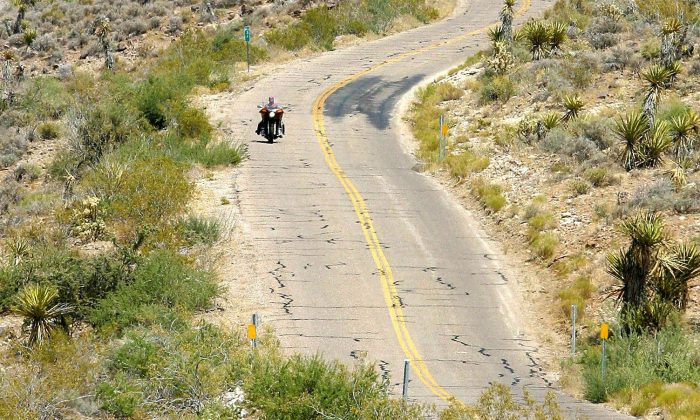 A lone motorcycle rider travels on historic Route 66 across the western Arizona desert on the approach to Oatman, AZ, 12 July 2003. (ROBYN BECK/AFP/Getty Images)