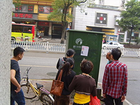 Local residents reading notice that demands an independent autopsy for Xu Chensheng and that the pepetrators be brought to justice. (Minghui.org)