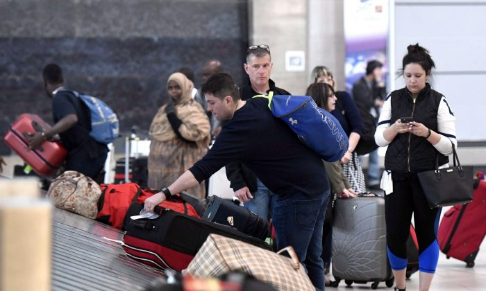 Travellers pick up their luggage at the Ottawa Airport on May 16, 2017. The federal government is introducing legislation for a passenger bill of rights that will set guidelines for how airline passengers are treated. (The Canadian Press/Justin Tang)