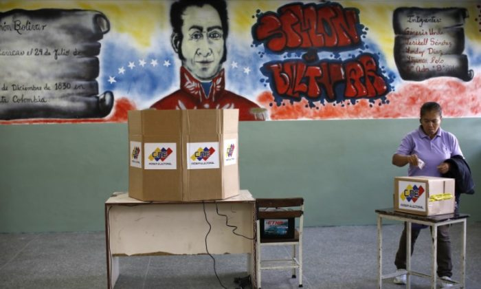 A woman casts her vote at a polling station during the Constituent Assembly election in Caracas, Venezuela, July 30, 2017. (Reuters/Carlos Garcia Rawlins)