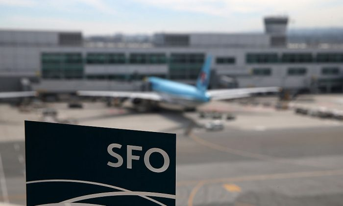 A plane parked at the international terminal is seen through the window of a sky train station at San Francisco International Airport. (Photo by Justin Sullivan/Getty Images)